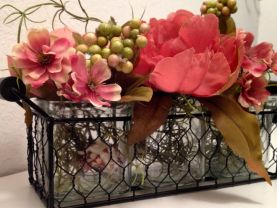 Wedding coral floral centerpiece or decoration.  Glass square vases nestled in a wire basket with dark wood handles